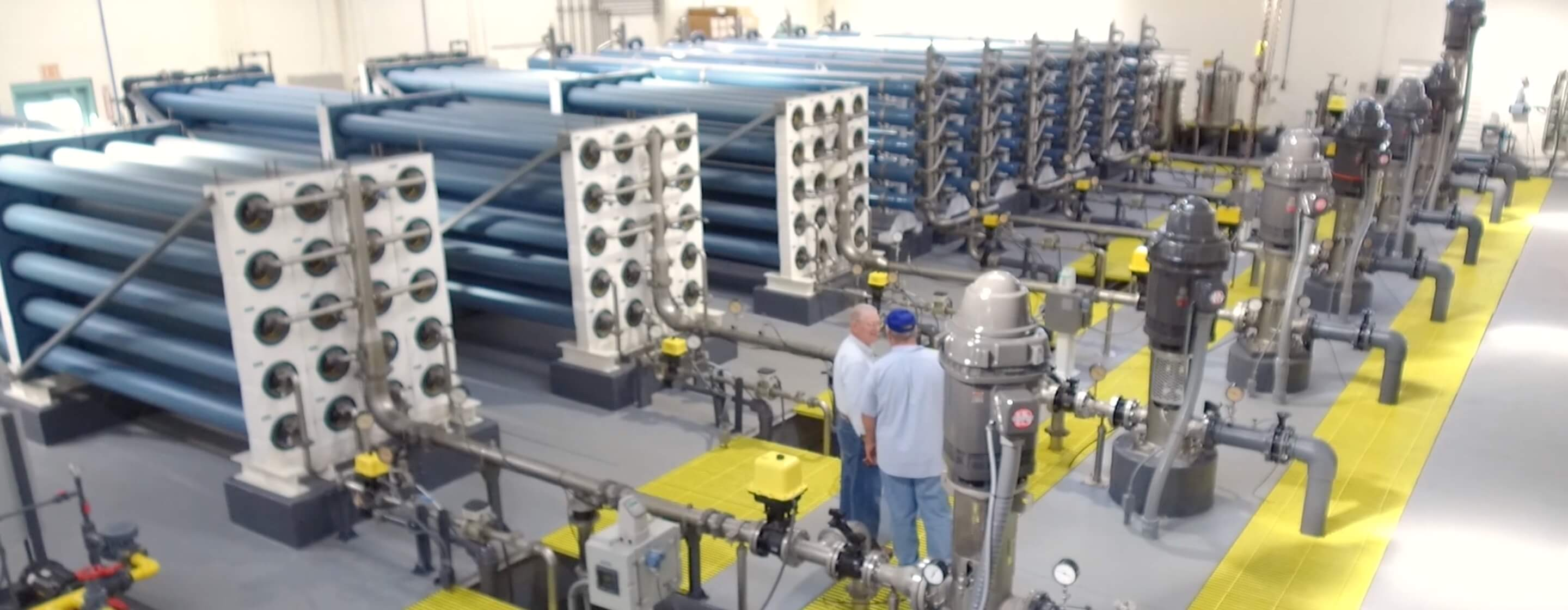 Multiple arrays of stacked reverse osmosis elements in a industrial water-treatment room, with two men consulting together