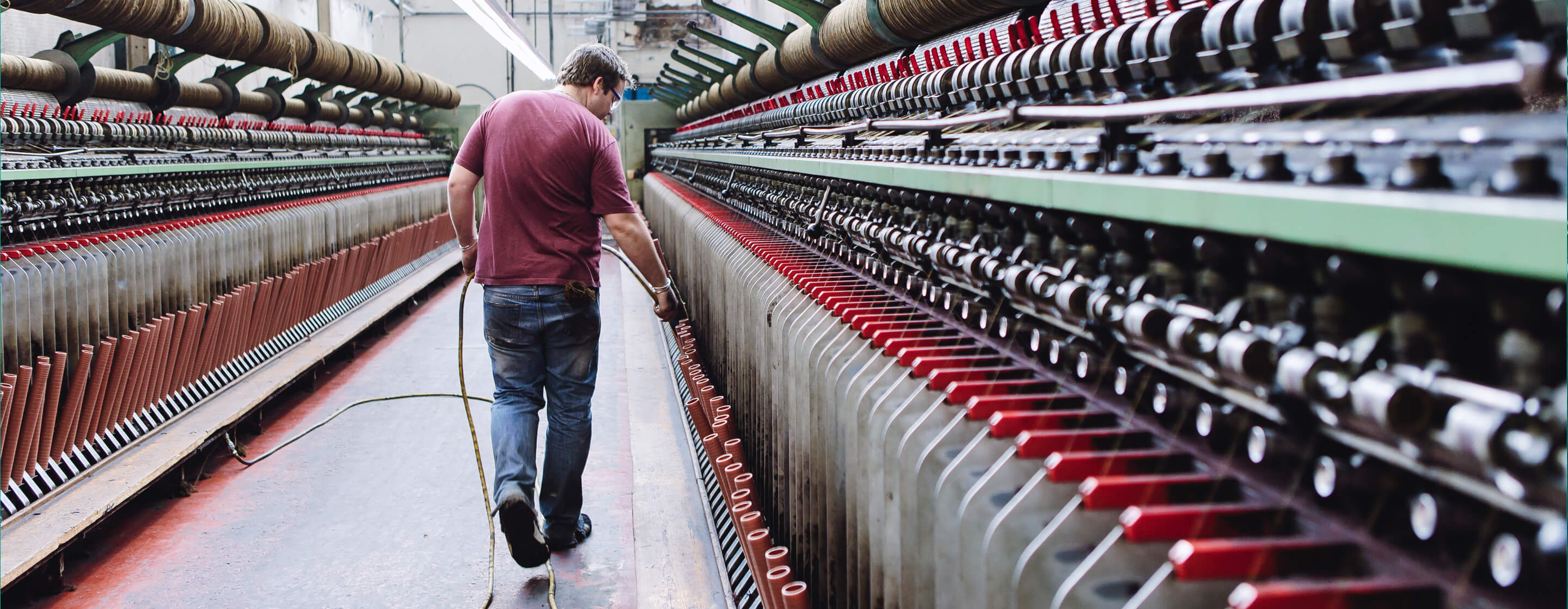 Man in t-shirt and jeans tending to large industrial textile looms in the textiles industry