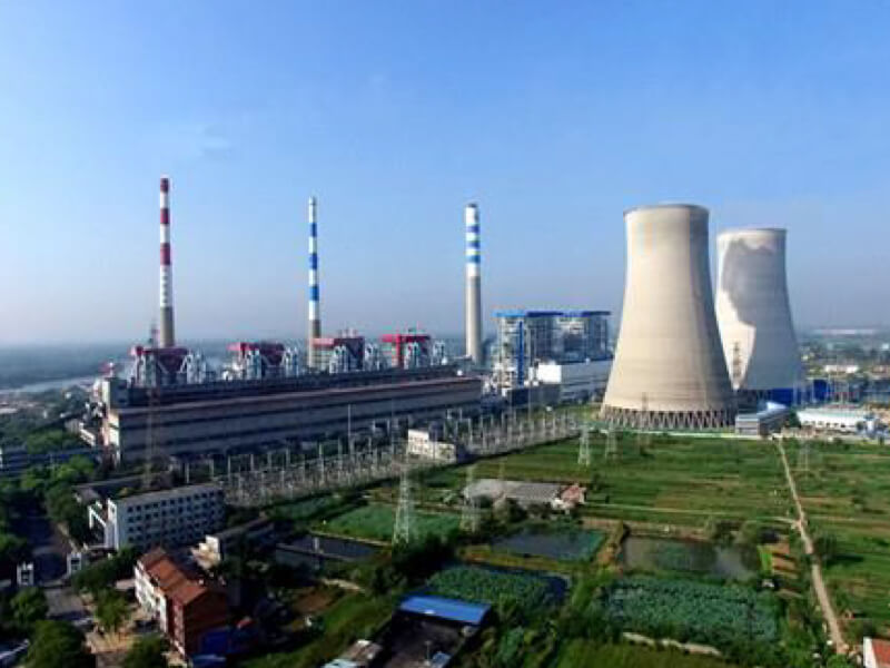 Aerial view of the Guodian Hanchuan power plant complex with two cooling towers, three striped smokestacks, grassy areas, buildings, pipes and roads