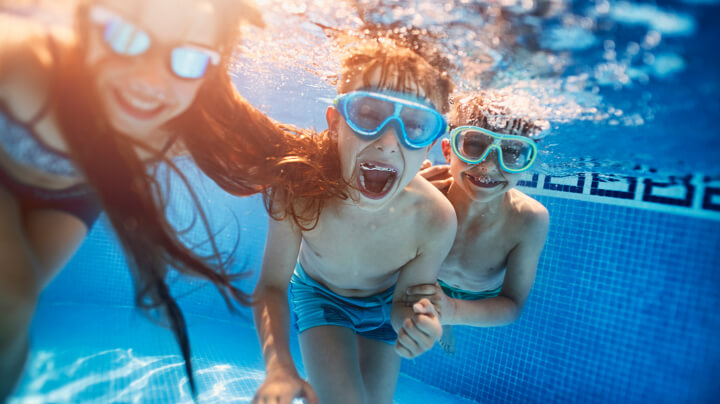 Underwater view of three smiling children with swimming goggles playing and blowing bubbles in a swimming pool