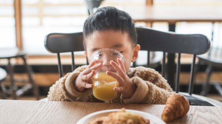 Young boy sitting at a table for his breakfast food and beverage, sipping a glass of orange juice